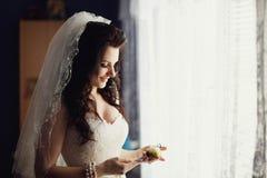 Bröllopboutonniere i händerna av den charmiga bruden Royaltyfria Bilder