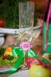Bröllopbrudexponeringsglas som dekoreras med rosa färger, blommar och gör grön bandet garnering Royaltyfri Fotografi