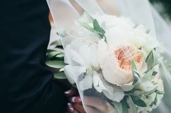 Bröllopbukett av kräm- pioner i händerna av bruden under skyla Arkivfoton