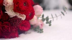 Bröllopbukett av röda och vita blommor på insnöade vintergröna conferous trän Slut och makrosikt av mjuka rosor på