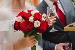 Bröllopbukett av röda och vita rosor i handen av bruden och ett exponeringsglas av champagne i den annan handen royaltyfri bild