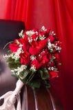 Bröllopbukett av vita nya rosor på hörnet av en soffa på en scharlakansröd bakgrund Royaltyfria Bilder