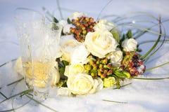 Bröllopbukett av vita och röda blommor och två exponeringsglas av champagne på snö Arkivbilder