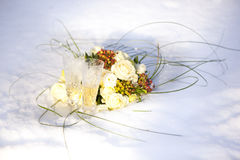 Bröllopbukett av vita och röda blommor och två exponeringsglas av champagne på snö Arkivfoto
