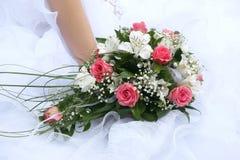 Bröllopbukett bruden på bakgrund av hennes klänning Royaltyfria Bilder