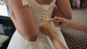 Bröllopbukett in i korg Brudtärna som binder pilbågen på bröllopsklänningen Händer för kvinna` s snör åt upp det siden- bandet på arkivfilmer