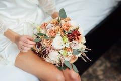 Bröllopbukett in i korg En kvinna i en vit bröllopsklänning som rymmer en bukett av blommor i hennes händer arkivbild