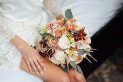 Bröllopbukett in i korg En kvinna i en vit bröllopsklänning som rymmer en bukett av blommor i hennes händer royaltyfria bilder