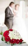 Bröllopbukett med bröllopparen i bacen Arkivfoto
