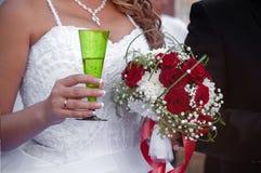 Bröllopbukett med rosor och ett exponeringsglas av champagne Fotografering för Bildbyråer