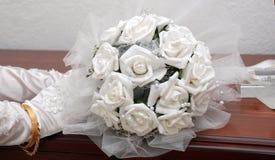 Bröllopbukett med vita rosor i händer för en brud Arkivfoto