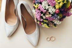 Bröllopbukett nära skorna och vigselringarna för brud` s Royaltyfria Foton