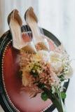 Bröllopbukett och brud- skor på en stol Royaltyfri Bild