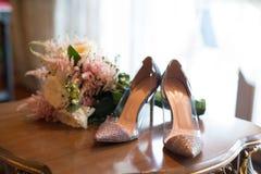 Bröllopbukett och brud- skor på en tabell Arkivbild