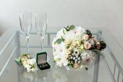 Bröllopbukett och delikat boutonniere med lilla rosor och Brunei och en grön ask med vigselringar Royaltyfria Bilder