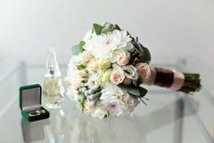 Bröllopbukett och delikat boutonniere med lilla rosor och Brunei och en grön ask med vigselringar Royaltyfria Foton