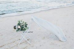Bröllopbukett på en stol på kusten Arkivbild
