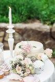 Bröllopbukett på en tabell bredvid kakan royaltyfri foto