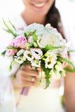 Bröllopbuketten räcker in av brud Arkivfoto