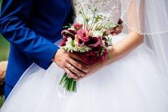 Bröllopbuketten av burgundy blommar i brud` s och händer för brudgum` s Arkivfoto
