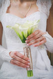 Bröllopbuketten av den vita callaen blommar lilly i händer av den unga bruden Arkivbilder