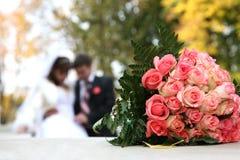 Bröllopbuketten ligger på bakgrunden av bruden och brudgummen Arkivfoto