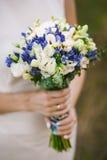 Bröllopbuketten räcker in av brud Arkivbild