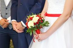 Bröllopbuketten räcker in av brud Bruden och brudgummen i registreringskontoret Royaltyfri Bild