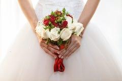 Bröllopbuketten räcker in av bruden Arkivfoto