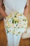 Bröllopbuketten räcker in av bruden Arkivbild