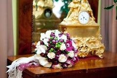 Bröllopbukettlögn på tabellen nära den forntida klockan royaltyfria foton
