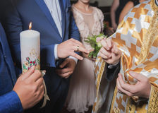 Bröllopceremoni av att sätta på av cirklar på fingrar, brudgummen och bruden Royaltyfria Foton