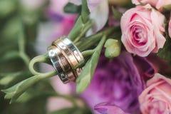 Bröllopcirklar med dimonds, bukettcolorfullrosor på en bakgrund royaltyfria bilder