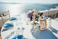Bröllopdekor av tabeller på ön av Santorini i guld-, blått- och vitfärger Royaltyfri Bild