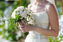 Bröllopbuketten i räcker av brud Arkivfoton