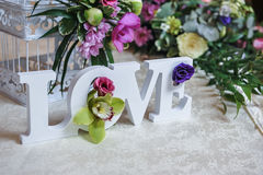 Bröllopdekor, FÖRÄLSKELSEbokstäver och blommor på tabellen Nya blommor och FÖRÄLSKELSEgarnering på den festliga tabellen Lyxig br arkivfoton
