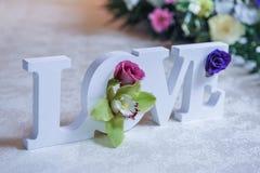Bröllopdekor, FÖRÄLSKELSEbokstäver och blommor på tabellen Nya blommor och FÖRÄLSKELSEgarnering på den festliga tabellen Lyxig br Arkivbilder