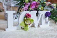 Bröllopdekor, FÖRÄLSKELSEbokstäver och blommor på tabellen Nya blommor och FÖRÄLSKELSEgarnering på den festliga tabellen Lyxig br Fotografering för Bildbyråer