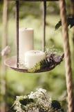 Bröllopdekor med blommor och stearinljus i skogen royaltyfria bilder