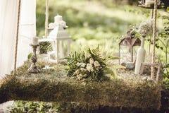 Bröllopdekor med blommor och stearinljus i skogen royaltyfri bild
