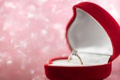 Bröllopdiamantcirkeln i röd hjärta formade gåvaasken arkivbilder