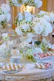 Bröllopefterrätttabell med kakor och vita blommor Arkivfoto