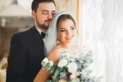 Bröllopfotoforsen av nygifta personerna kopplar ihop att posera i ett härligt hotell arkivfoto