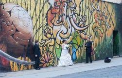Bröllopfotograf & klienter framme av grafittiväggen royaltyfri foto