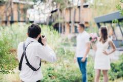 Bröllopfotografen tar bilder av par som är förälskade i natur i sommar arkivbilder