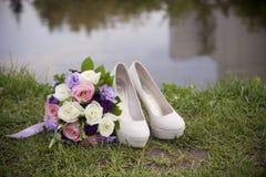 Bröllopfotografi Skor och en bukett av bruden arkivfoton