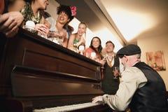 Bröllopgäster som har gyckel med pianot Royaltyfria Bilder