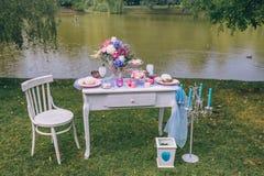 Bröllopgarnering i stilen av bohoen, blom- ordning, dekorerad tabell i trädgården nära sjön festlig tabell Arkivfoto