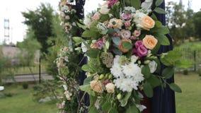 Bröllopgarneringar för utomhus- bröllopceremoni Träbågen dekorerade med vita och rosa rosor Bin och humlor lager videofilmer