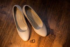 Bröllopgarneringdetaljer Guldbröllopcirklar och eleganta brud- skor Royaltyfria Bilder